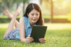 Beauty asian woman using digital tablet on grass. In outdoor park. nature outdoors background. people and technology concept Royalty Free Stock Image