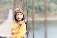 Woman on the wooden bridge. Beauty asian woman in yellow wear and black jeans and wool hat on the wooden bridge Stock Images