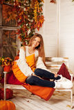 Beauty autumn woman smiling on the porch of yellow and orange au Stock Photos