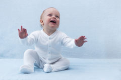 Beauty baby boy with expanded arms. Cute smiling joyful infant kid. Laughing toddler Royalty Free Stock Photos