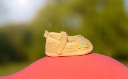 Beauty baby shoes on the mother's belly Stock Photography