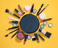 Beauty background with cosmetics for makeup. Photo of black makeup bag with cosmetic products on yellow background. Copy space for your text stock photo