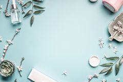 Beauty background with facial cosmetic products, leaves and cherry blossom on pastel blue desktop background. Modern spring skin care layout, top view, flat stock photography