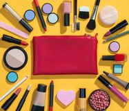 Beauty background with makeup cosmetic products. Photo of red makeup bag with cosmetic products on yellow background. Copy space for your text royalty free stock photography