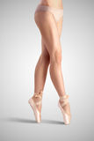 Beauty and balance. A graceful female classical ballet dancer on pointe shoes wearing beige satin underwear and standing on toes on a neutral light studio Stock Image