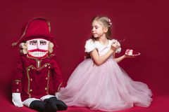 The beauty ballerina standing with nutcracker. A Beauty Ballerina standig near nutcracker at red studio Stock Images