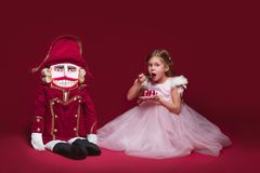 The beauty ballerina standing with nutcracker. A Beauty Ballerina standig near nutcracker at red studio Stock Photo