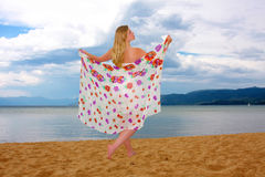 Beauty at the Beach. Beautiful young woman posing with a colorful scarf on a deserted beach against a cloud filled sky Stock Photo