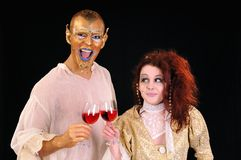 Beauty and beast. Young man and girl toasting with artistic painted faces Stock Images