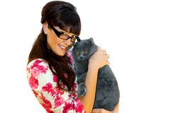 Beauty and the beast. Beautiful girl in glasses with fat cat on white background Stock Photography