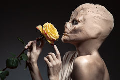 Beauty and the beast. Ugly witch with beautiful flower in hand. Stock Photo