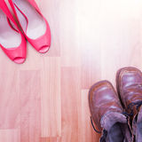 Beauty and the Beast. Womens shoes and mens boots opposite each. New pink womens shoes and old mens boots Stock Photos