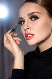 Beauty. Beautiful Woman Applying Black Mascara On Eyelashes Royalty Free Stock Photos
