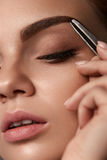 Beauty. Beautiful Woman Shaping Eyebrows With Tweezers. Beauty Woman Makeup. Closeup Of Beautiful Glamorous Sexy Woman Face With Closed Eye Plucking Eyebrow With Stock Image