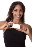 Beauty in a black dress holds a business card. Attractive woman smiling with a blank business card Royalty Free Stock Image
