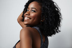Beauty black woman with curly hair and metallic eyeshadows. Black woman touches her curly hair and smiling royalty free stock image