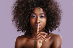 Beauty black woman making shhh! on the violet background. In studio Royalty Free Stock Photography