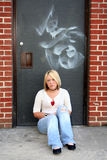 Beauty And Blight. Serious young blond woman, sitting against the spray-painted door of a school Royalty Free Stock Image