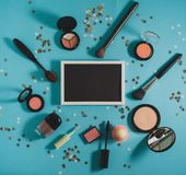 Beauty blog concept. Cosmetics - powder, blush, brushes, mascara, shadows on a blue background. In the center is a black board for text. Beauty blog concept Royalty Free Stock Photo
