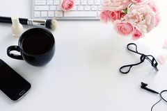 Beauty blog concept. Female make up accessories. Cup of cofee and bouquet of pink roses on white background. Flat lay, top view feminine desk, workspace with Royalty Free Stock Photo