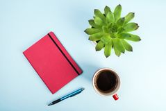 Beauty blog concept photo. Green plant, notebook, pen and cup of coffee on pink background. Green plant, red notebook, pen and cup of black coffee on blue stock photography