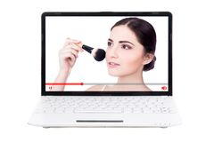 Beauty blog concept - woman showing how to apply make up on laptop screen. Beauty blog concept - beautiful woman showing how to apply make up on laptop screen royalty free stock photo