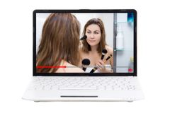 Beauty blog - young woman showing how to apply make up in video on laptop screen. Beauty blog concept - young woman showing how to apply make up in video on stock photo