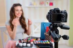Beauty blogger holding lip gloss stock photography