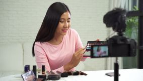 Beautiful woman use brush while review make up tutorial broadcast live video to social network by internet.