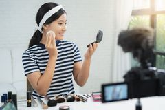 Beauty blogger present beauty cosmetics while sitting in front camera for recording video. Beautiful woman use powder. Beauty blogger present beauty cosmetics royalty free stock photos