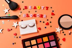 Beauty blogger text on an orange background. Professional trendy makeup products with cosmetic beauty products,  eye shadows, eye. Lashes, brushes and tools royalty free stock photos