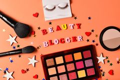 Beauty blogger text on an orange background. Professional trendy makeup products with cosmetic beauty products,  eye shadows, eye. Lashes, brushes and tools stock images