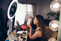 Beauty blogger woman showing cosmetics and telling makeup turtorial and taking video on camera.  Royalty Free Stock Image
