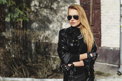 Beauty blond girl in leather jacket. Portrait biker sexy woman blonde in sunglasses and black jacket Stock Image