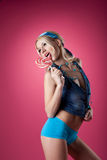 Beauty blond girl lick candy on pink background Stock Photo