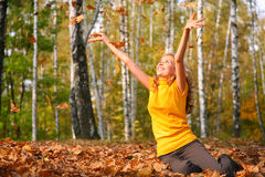 Beauty blond girl throws leaves in park Royalty Free Stock Photos