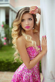 Beauty blond model girl in fashion pink dress with makeup and lo Stock Photos