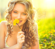 Beauty blond model girl smelling dandelion Stock Images
