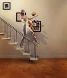 Beauty blond woman walking down stairs drops food. Young beautiful blond hair women in elegant cream-coloured dress while walking down the stairs lost the Royalty Free Stock Image