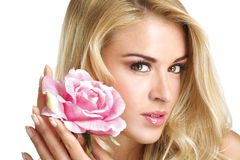 Beauty blond young woman showing a fresh flower on white Royalty Free Stock Images