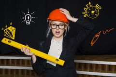 Beauty blonde businesswoman with designer or architect staff is standing against concrete wall with startup sketch on it. Concept of project launch stock images