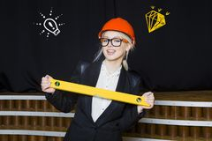 Beauty blonde businesswoman with designer or architect staff is standing against concrete wall with startup sketch on it. Concept of project launch royalty free stock photos