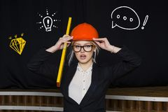Beauty blonde businesswoman with designer or architect staff is standing against concrete wall with startup sketch on it. Concept of project launch royalty free stock images