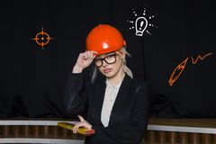 Beauty blonde businesswoman with designer or architect staff is standing against concrete wall with startup sketch on it. Concept of project launch stock photos