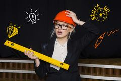 Beauty blonde businesswoman with designer or architect staff is standing against concrete wall with startup sketch on it. Concept of project launch royalty free stock photo