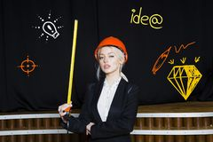 Beauty Blonde Businesswoman With Designer Or Architect Staff Is Standing Against Concrete Wall With Startup Sketch On It Royalty Free Stock Photos