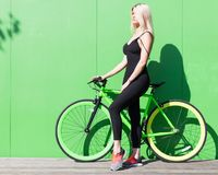 Beauty blonde girl with long hair in a black tight-fitting sexy outfit and sneakers posing with a fashionable fix. Bicycle background of a green wall on a sunny Royalty Free Stock Photo