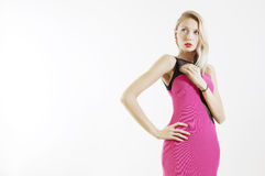 Beauty blonde girl posing in pink dress. Royalty Free Stock Image