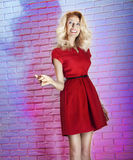 Beauty blonde girl posing in red dress. Stock Image
