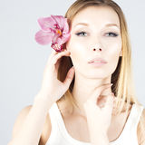 Beauty blonde with pink flower in hair. Clear and fresh skin. Beauty face. Royalty Free Stock Images